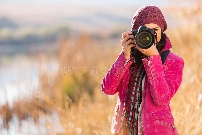 Woman photographing autumn. Young woman photographing outdoors in autumn royalty free stock photography