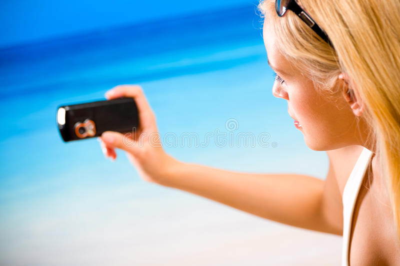 Woman photographing by cell phone. On beach royalty free stock image