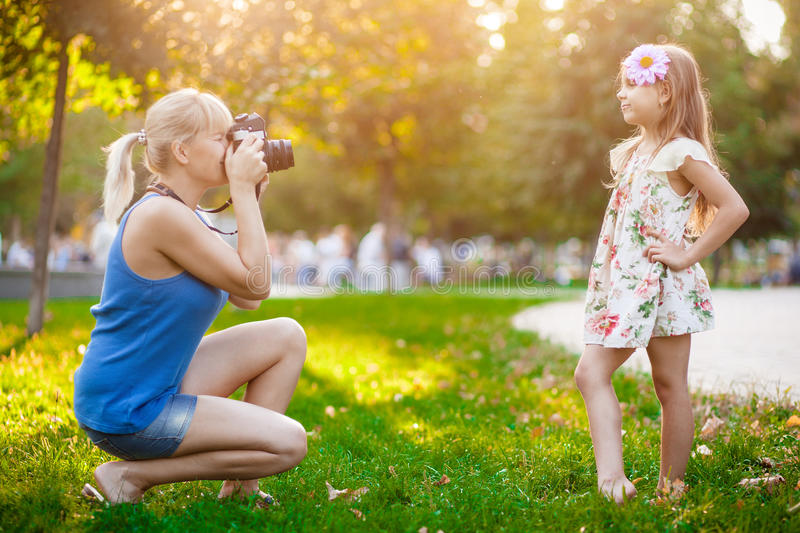 Woman photographing child stock photos