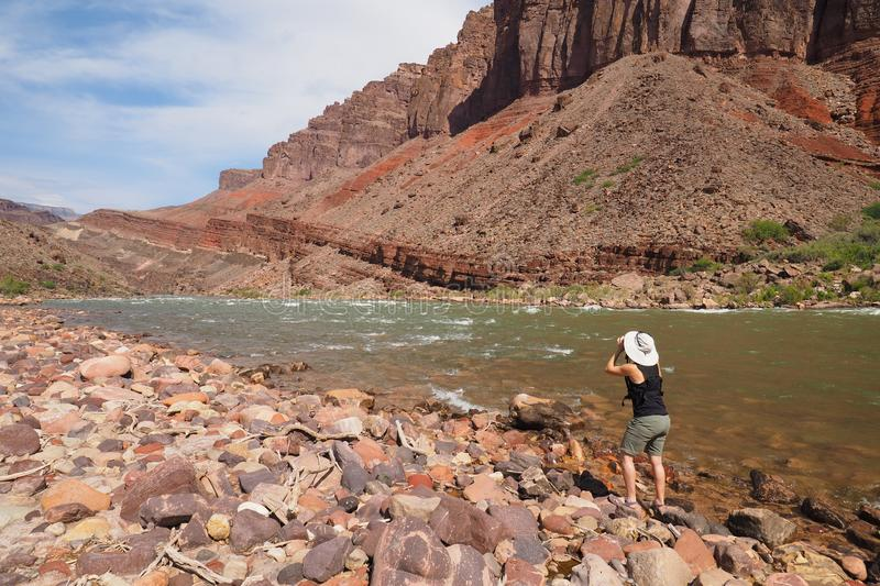 Woman photographing the Colrado River and inner canyon in the Grand Canyon. royalty free stock image