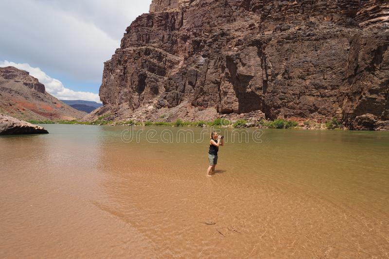 Woman photographing the Colrado River and inner canyon in the Grand Canyon. stock photo