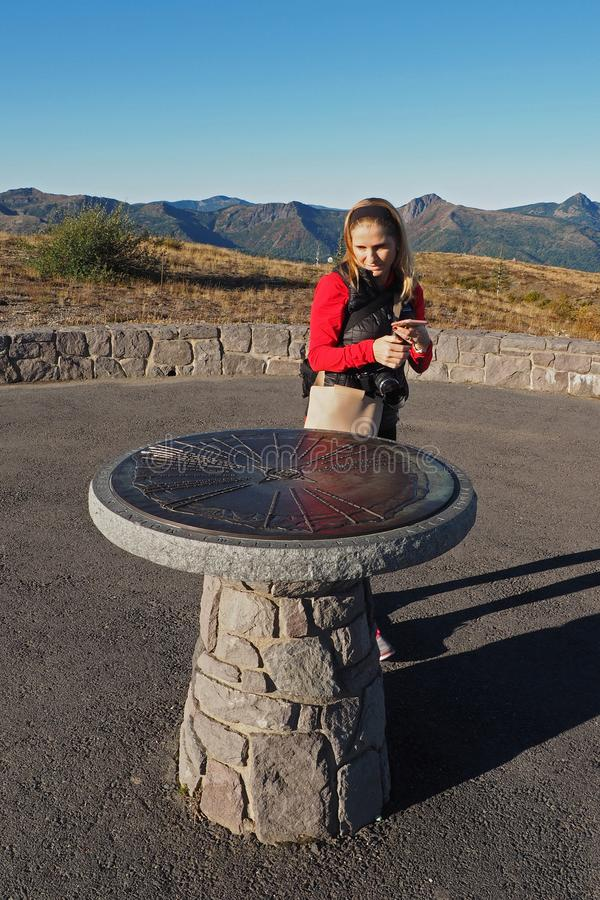 Woman photographing a directional monument at Mount Saint Helens National Volcanic Monument. royalty free stock photos