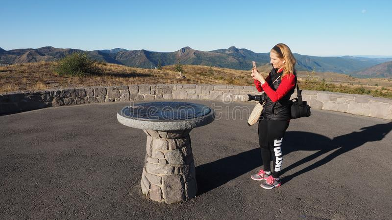 Woman photographing a directional monument at Mount Saint Helens National Volcanic Monument. royalty free stock image