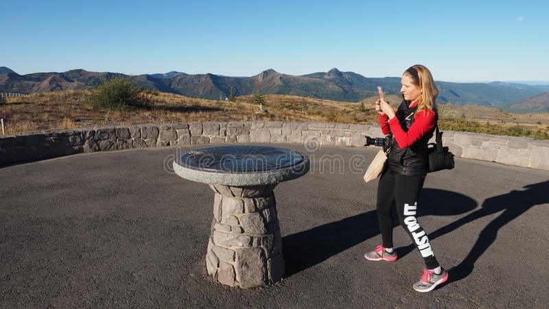 Woman photographing a directional monument at Mount Saint Helens National Volcanic Monument. stock image