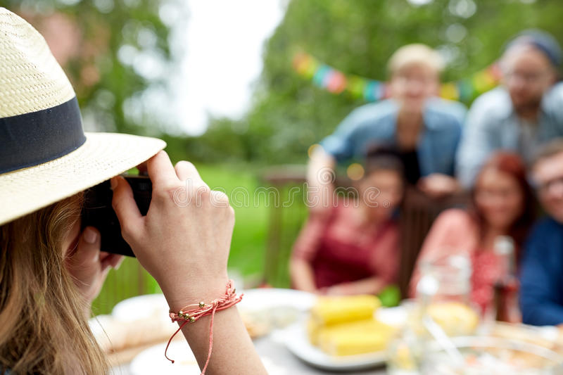 Woman photographing friends at summer garden party. Leisure, holidays and people concept - happy friends having dinner and photographing at summer garden party royalty free stock photos