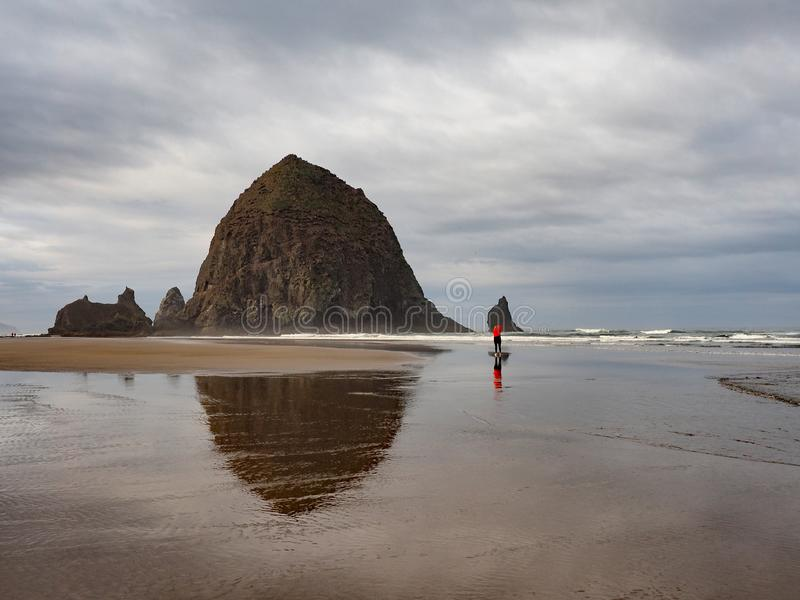 Woman photographing Haystack Rock on Cannon Beach, Oregon. royalty free stock photo