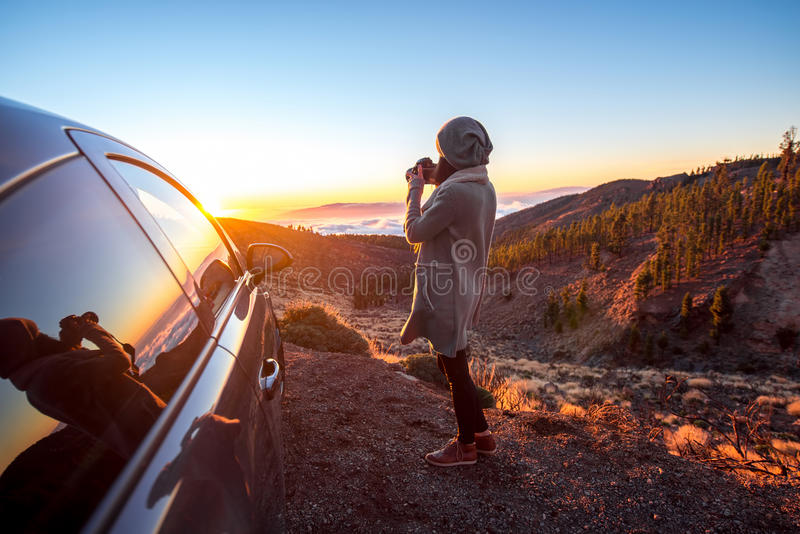 Woman photographing landscape standing near the car. Woman photographing beautiful landscape above the clouds near the car on the sunset stock photos
