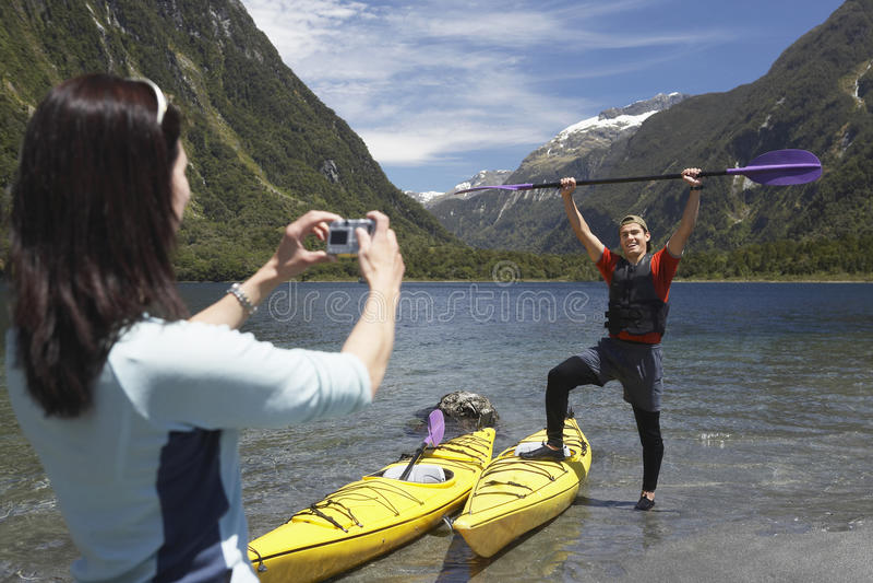 Woman Photographing Man Raise Oar At Mountain Lake stock photos