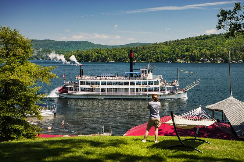 WOMAN PHOTOGRAPHING PADDLE STEAM BOAT ON LAKE FROM SHORE royalty free stock photography