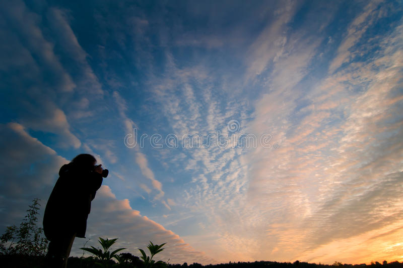 Woman photographing the sunrise stock photos