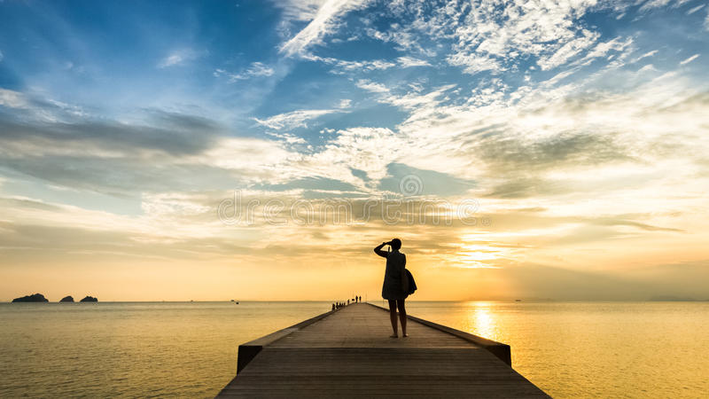 Woman photographing sunset on the pier in the sea. On tropical island stock image
