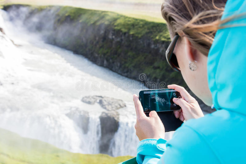 Woman photographing a waterfall with a mobile phone stock images