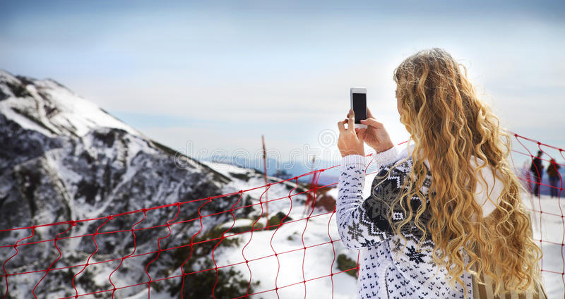 Woman photographing winter landscape mountains and snow with cell phone royalty free stock photography