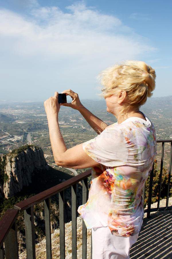 Woman photographs the beautiful surroundings royalty free stock photography