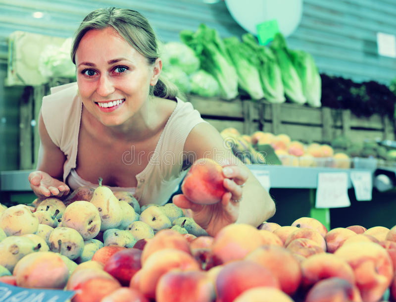 Woman picking aromatic peaches stock images