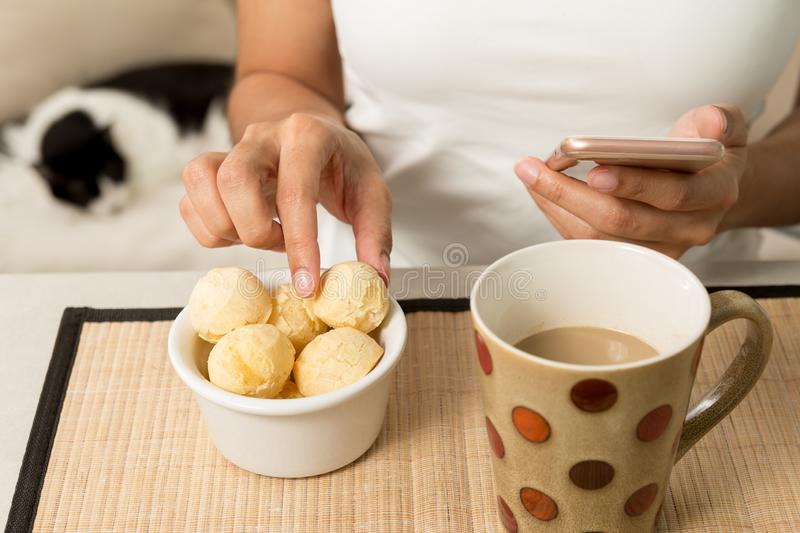 Woman picking bread cheese known as Pao de Queijo in Brazil an royalty free stock photos