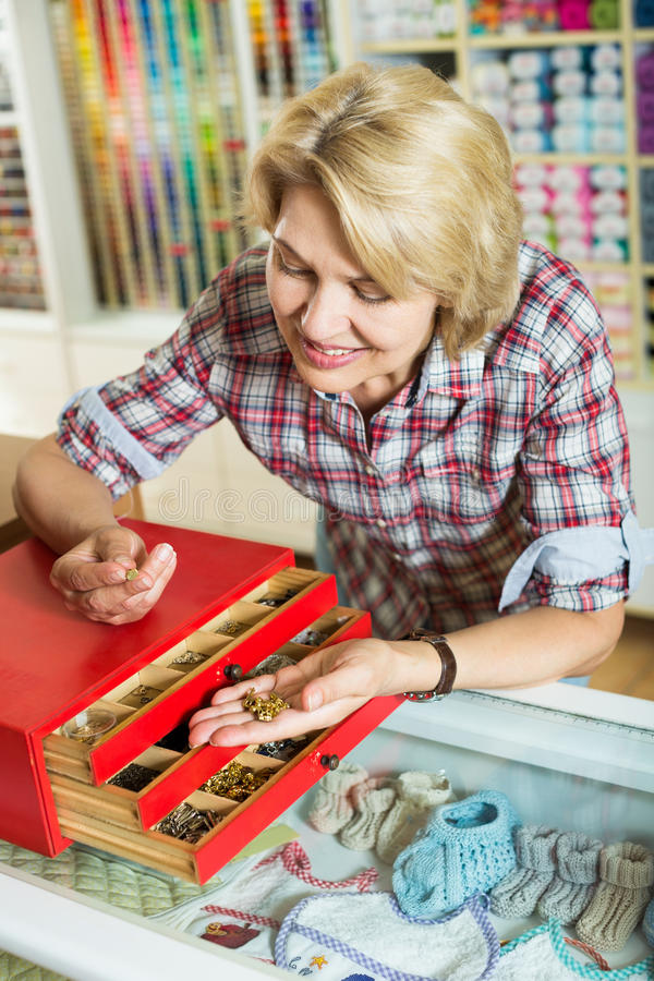 Woman picking buttons and clasps stock images
