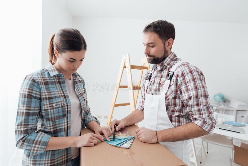 Woman picking a color for her walls. Woman picking a color for her house walls, a professional painter and decorator is showing her color swatches royalty free stock image