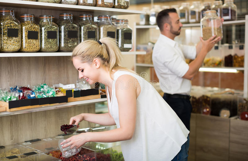 Woman picking dried fruits in store. Cheerful young female customer buying various candied fruits in store with ecological goods stock photos