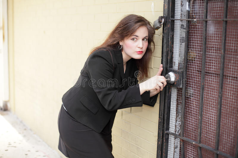 Woman picking the lock. Image of a businesswoman trying to pick a lock royalty free stock photos