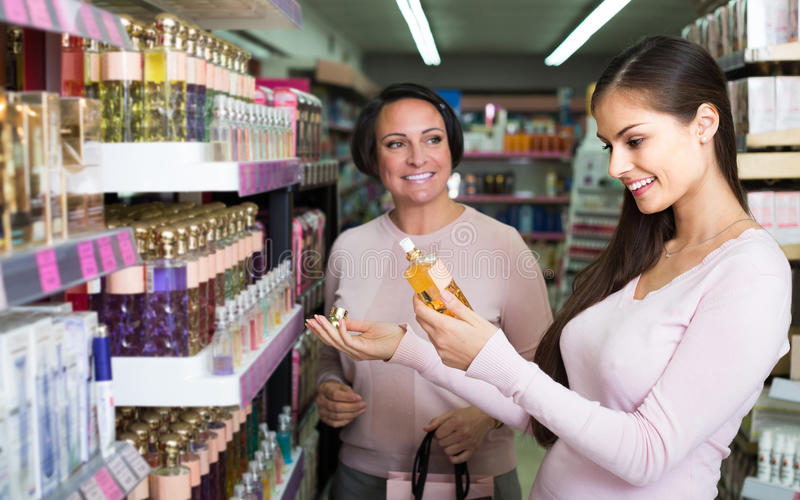 Woman picking scented spray from shelf in cosmetics store. Happy american women picking scented spray from shelf in cosmetics store royalty free stock photography