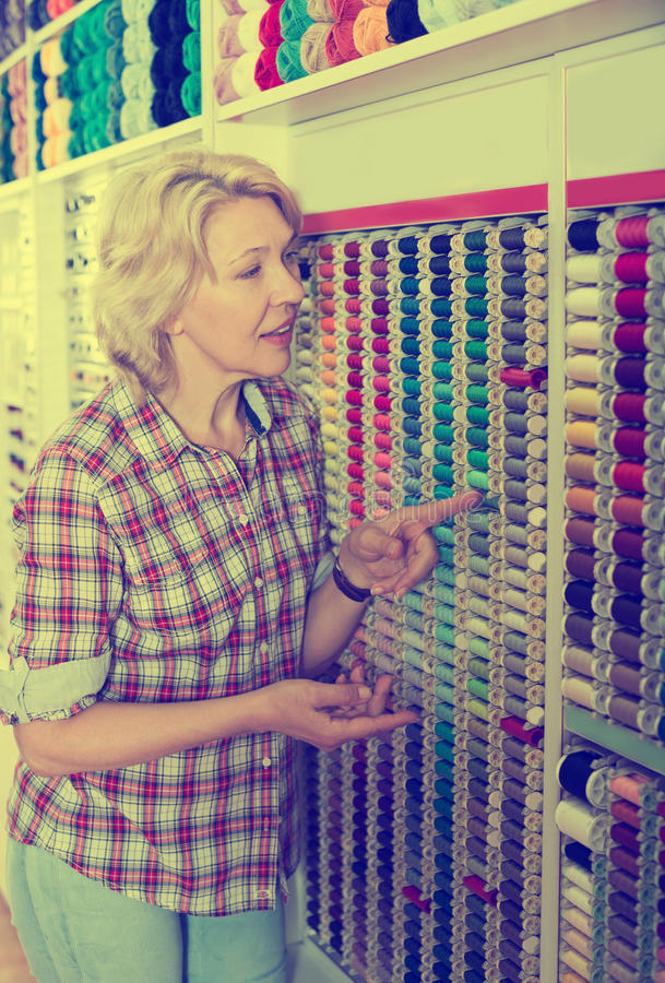 Woman picking sewing tools stock photos