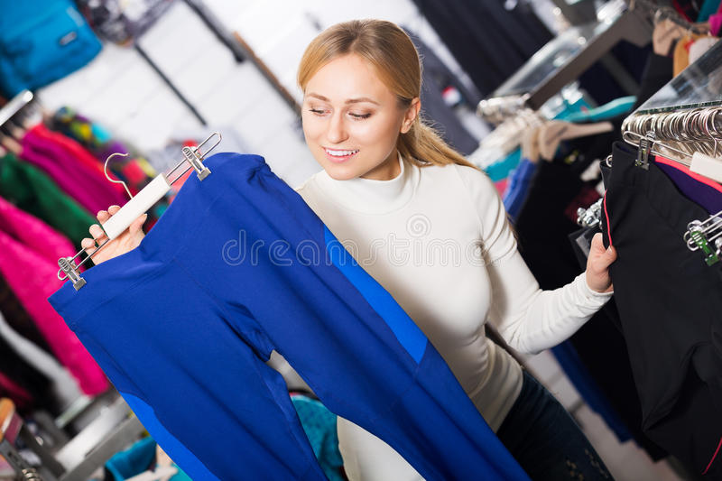 Woman picking a sporty pants. Blonde young woman picking a sporty pants in the shop royalty free stock images