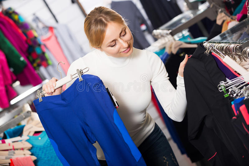 Woman picking a sporty pants. Happy young woman picking a sporty pants in the shop stock photography