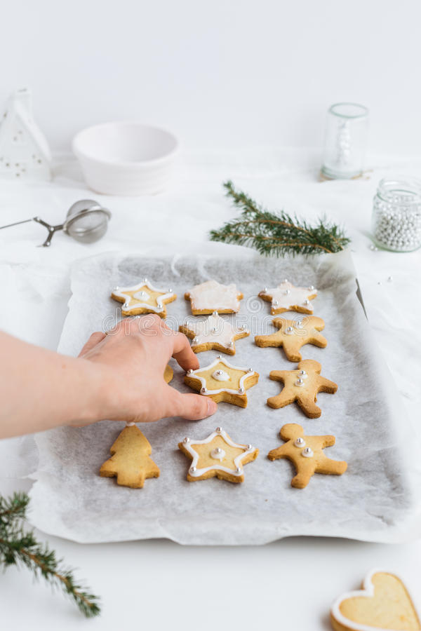 Download Woman Picking Up Decorated Christmas Biscuits From Baking Tray Stock Photo - Image of decoration, dessert: 83720320