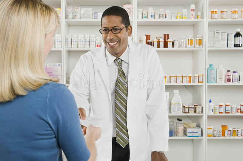 Woman Picking Up Prescription Drugs At Pharmacy royalty free stock photo