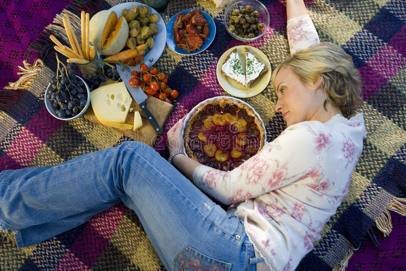 Woman on picnic blanket embracing tart, elevated view, full frame stock photo