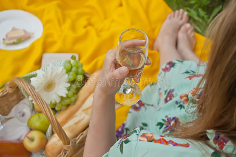 Woman on the picnic sits on the yellow cover and holds wine glass. Near picnic basket with food and fruits. Woman on the picnic sits on the yellow cover and royalty free stock photos