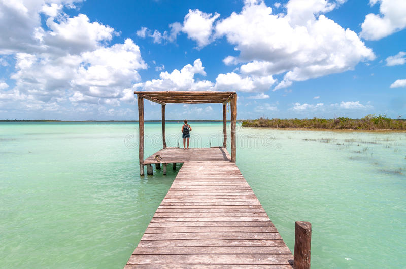Woman on pier in Caribbean Bacalar lagoon, Mexico stock images