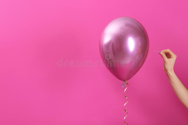 Woman piercing balloon with needle on color background, closeup. stock photography