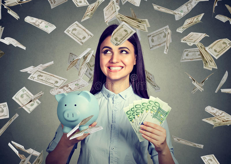 Woman with piggy bank and euro cash under dollar money rain. Young woman with piggy bank and euro cash under dollar money rain royalty free stock images