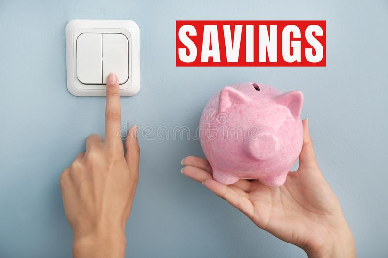 Woman with piggy bank switching off the light. Electricity saving concept royalty free stock photos