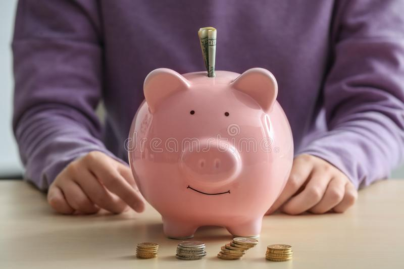 Woman with piggy bank at table. Savings concept royalty free stock image