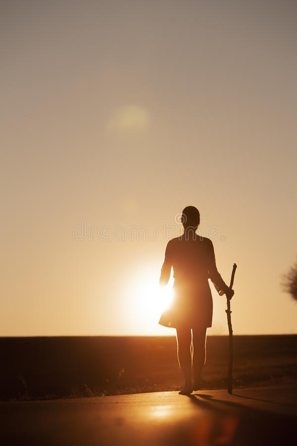 Woman at Pilgrimage. Looking at sunset and walking barefoot alone royalty free stock images