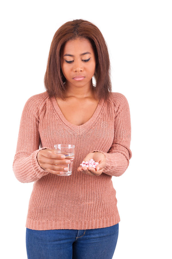 Woman with pills medicine tablets and glass of water. Isolated stock image