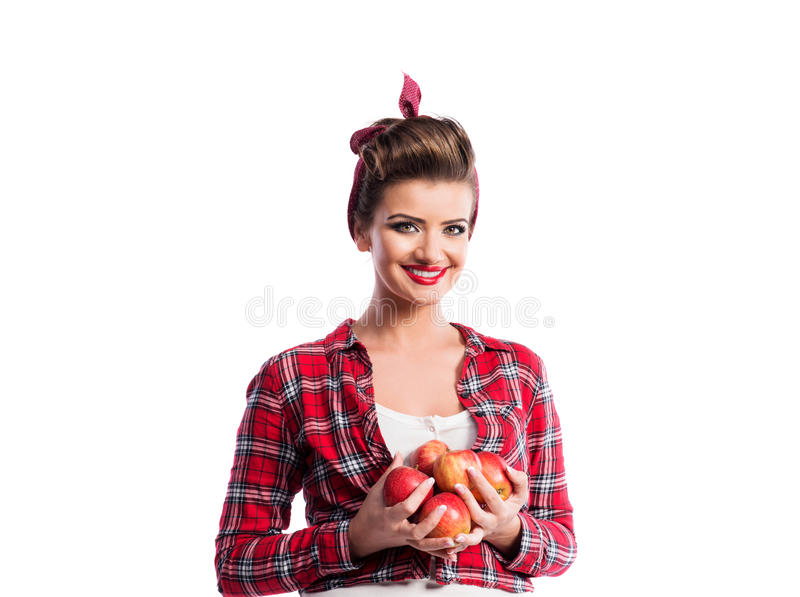 Woman, pin-up hairstyle holding armful of apples. Autumn harve royalty free stock photo
