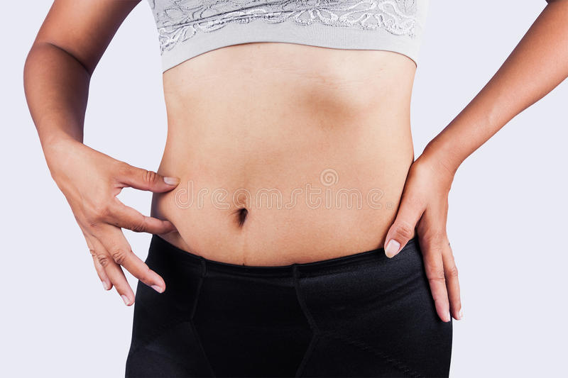 Woman pinching belly fat after weight loss stock photos