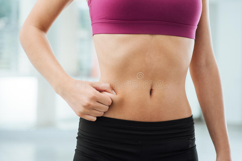 Woman pinching fat on her belly. Slim young woman pinching fat on her belly, fitness and weight loss concept royalty free stock image