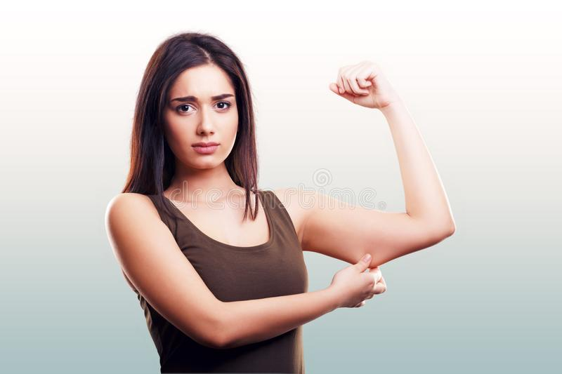 Woman pinching flabby fat arm skin. Excess on blue gray background royalty free stock photography