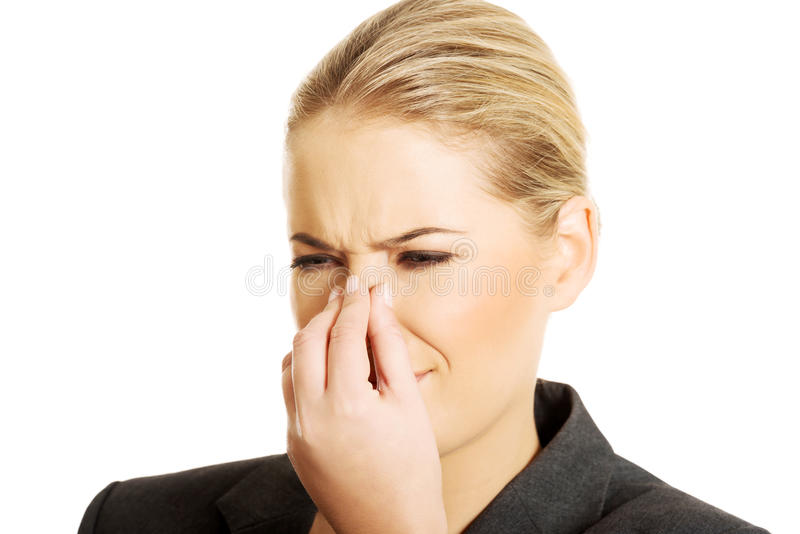 Woman pinching her nose. Because of disgusting smell stock photo