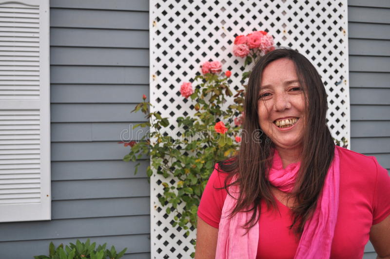 Woman in Pink. A middle age woman is smiling with pink clothes and a background of roses stock photography
