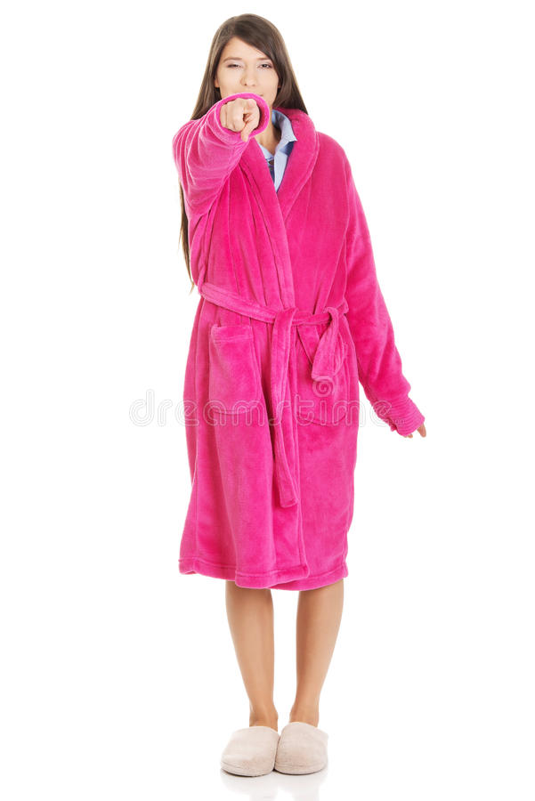 Woman in pink bathrobe pointing on you. Beautiful woman wearing pink bathrobe pointing on you royalty free stock image