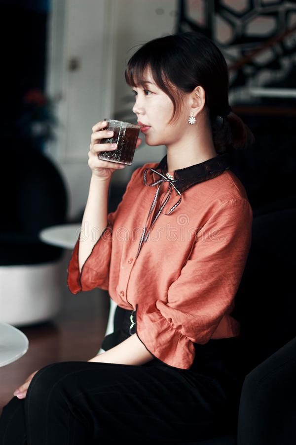 Woman in Pink and Black Dress Drinking Cola royalty free stock image