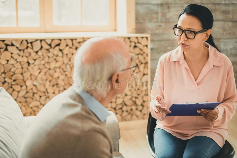 Woman in pink blouse having important conversation with old man. Carrying paper tablet. Woman in pink blouse having important conversation with old men sitting royalty free stock images