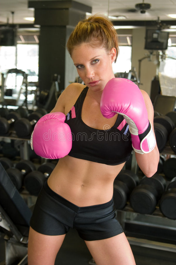 Woman In Pink Boxing Gloves 3. Beautiful, fit woman wearing hot pink boxing gloves stock photography