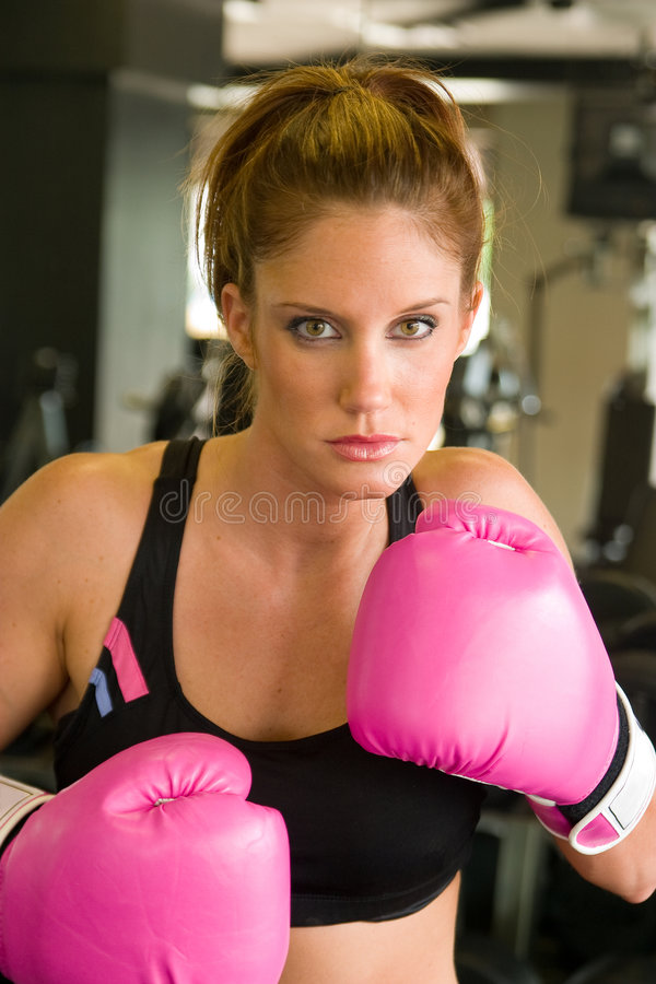 Woman In Pink Boxing Gloves 5. Beautiful, fit woman wearing hot pink boxing gloves stock photo